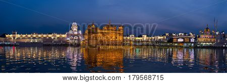 The Golden Temple at Amritsar Punjab India the most sacred icon and worship place of Sikh religion. Illuminated in the night reflected on lake.