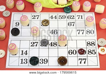 photograph of details of Russian vintage game Bingo or Lotto with white paper cards in the cells which contain numbers small wooden barrel on which is written the numbers green bag multi-colored buttons on the table red color