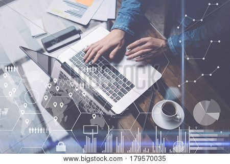 Man working at sunny office on laptop while sitting at the wooden table.Concept of digital screen, virtual worldwide connection icon, diagram, graph interfaces on background.Blurred, visual effects