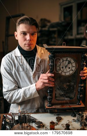 Watchmaker adjusts the mechanism of old wall clock