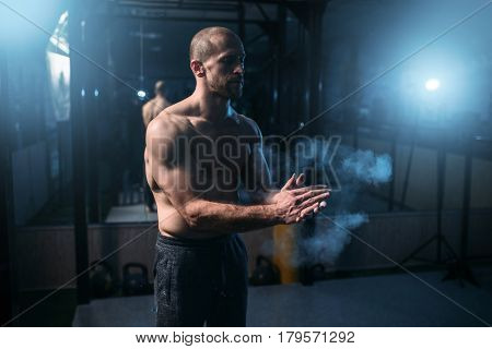 Male athlete rubs hands with talcum powder