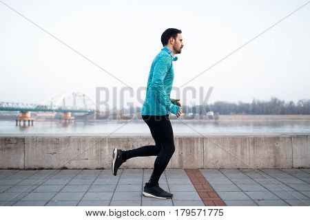 Sportsman in outfit running and jogging in city