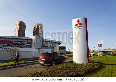 Prague, Czech Republic - March 31: Mitsubishi Motors Company Logo With Mazda Car In Front Of Dealers