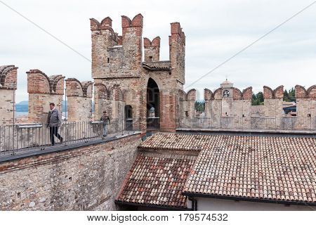 Tourists Walk On The Walls Of Castello Scaligero In Sirmione