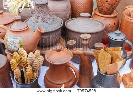 Diverse clay and wooden utensils on the counter at the fair city during the celebration of Carnival