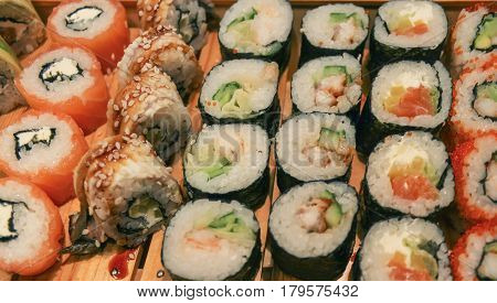 Japanese rolls on wooden plate close up