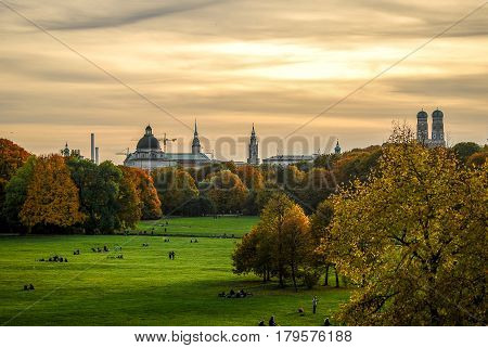 MunichGermany- October 242015: View of  downtown Munich's skyline at sunset while people stroll in  the Englischer Garten Park