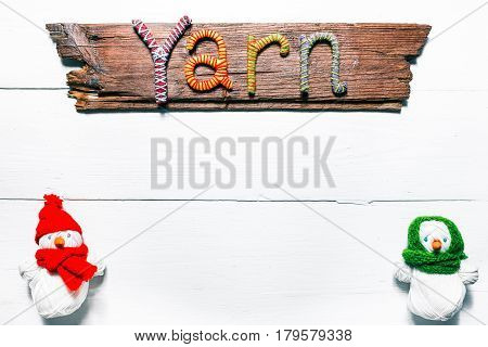 Knit shop background with title wood sign 'Yarn' of handmade letters and couple of handmade snowmen of yarn skeins. White wood background