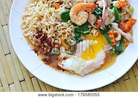 instant noodle dressing seafood gravy sauce and creamy egg yolk on plate