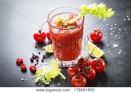 Traditional Bloody Mary cocktail. Alcoholic drink and ingredients at dark slate table.