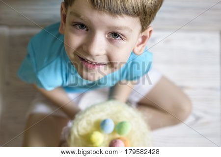 Cute Little Boy Holding A Nest With Colored Easter Eggs At Home On Easter Day. Celebrating Easter At
