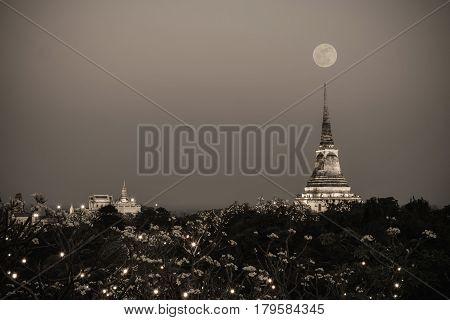 White pagoda in Phra Nakhon Khiri Historical Park with full moon at night Phetchaburi Thailand. Vintage tone