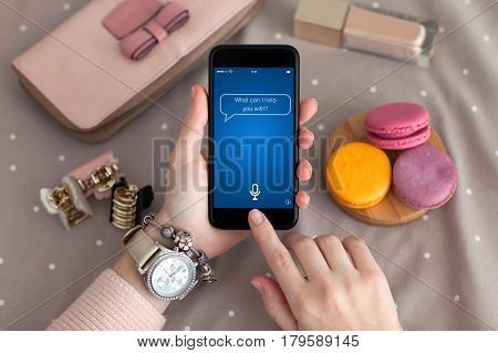 female hand jewelry holding phone with app personal assistant on screen