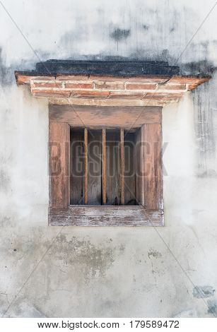 Rusty metal window with metal bars and wooden planks