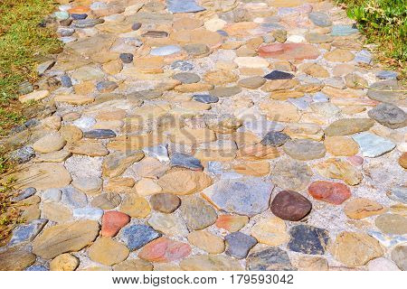 Pedestrian path paved with granite stone. Texture of natural stone. Village Bali Crete island Greece
