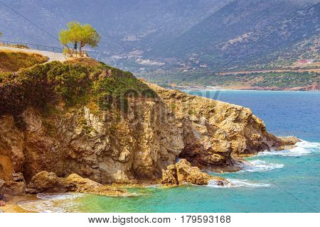Waves break on rocky shore. Coast and beach resort village. Road along a rocky cliff. Tourist beach resort in village of Bali Crete island Greece Beach Evita