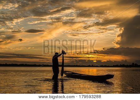 Fisherman is fishing by using fishing net on the river during evening sunset