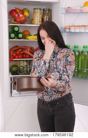 Angry and upset housewife looking into a pot with foul meal. Beautiful young girl near the fridge.