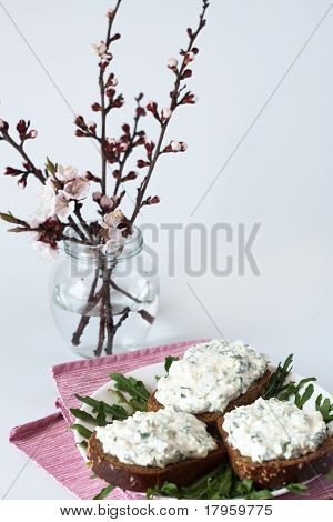 Cheese snack on rye bread, arugula and bouquet of blooming cherry branches poster