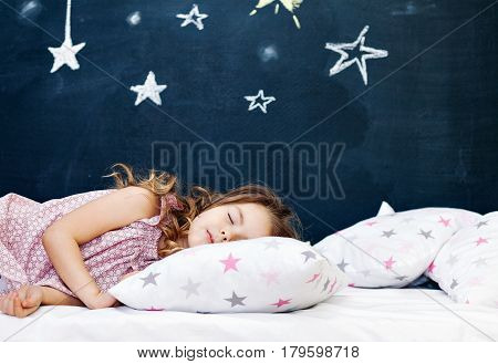 Cute little girl lying in the bed and sleeping. Horizontal indoors shot.