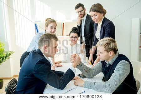 Arm wrestling in office between two workers
