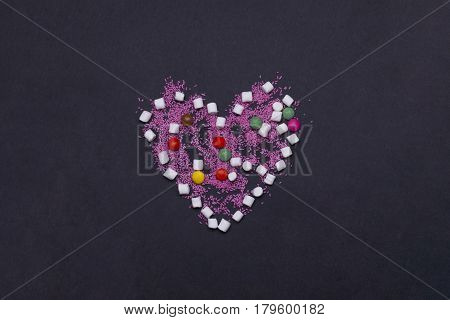 colorful tasty marshmallow zephyr and dragee sprinkles sweets in valentines day heart shape on grey background copy space