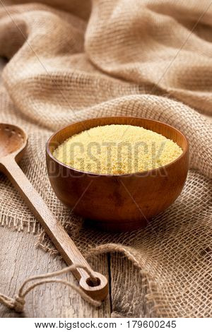 Couscous in a wooden bowl on a wooden background