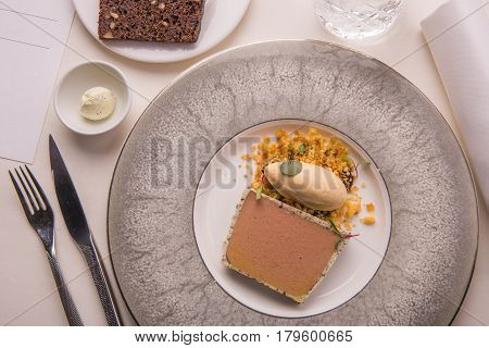 Laying of parfait from a liver of a guinea fowl with tableware, bread and oil