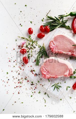 Raw Pork Loin chops on a cutting board with herbs, rosemary, thyme, chilli, salt, pepper on white cutting board