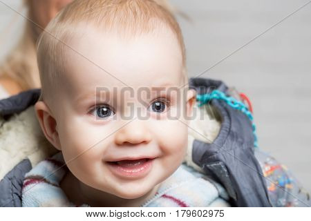 Cute happy baby boy little child with blond hair and big eyes on adorable smiling face in jacket on blurred background childhood and happiness