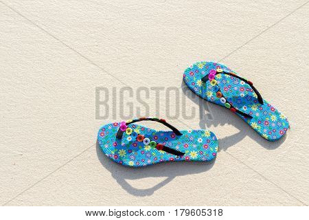 Thailand Similan Islands. Blue women's beach shoes with white sand blue sea and sky.