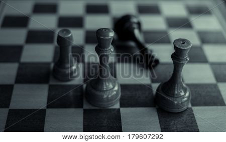 Chess game. Black king is checkmated and fallen on chessboard. game over. Old wooden chess. Black and white photo