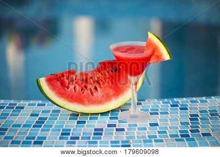 Glass of watermelon cocktail with watermelon slice near pool