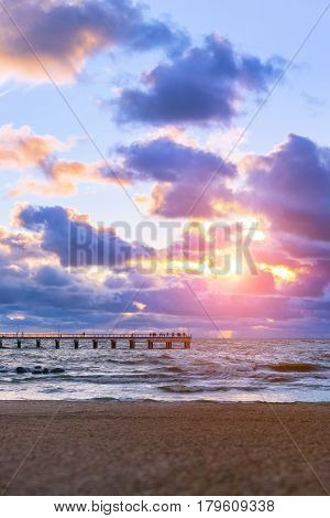 Sunset at Baltic sea in resort of Lithuania Palanga. Rays of sun shine through the low cumulus clouds. Pedestrian pier extends into the sea. Storm waves wash the sandy beach