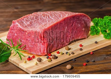 Big Raw Boneless Beef Meat With Pepper, Rosemary, Parsley On Wooden Table, Close Up