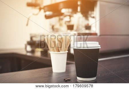 A glass of black coffee is on the table against the background of an electric coffee machine in a cafe.