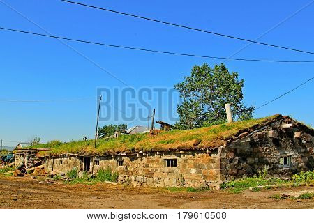 Old brick shed with a roof covered with a grass