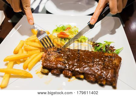 Girl Cutting Roasted Barbecue Pork Ribs, Focus On Sliced Meat