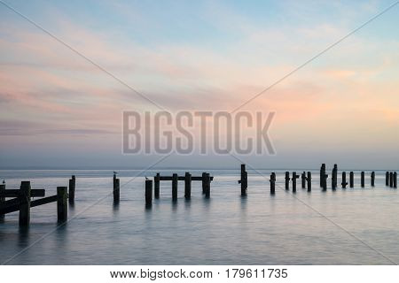 Stunning Peaceful Sea Landscape Of Old Derelict Pier Foundations At Sunrise