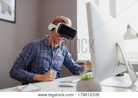 Smiling man having fun with the VR goggles in the office. Horizontal indoors shot.