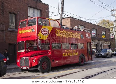 TORONTO,CANADA-NOVEMBER 01,2016: Red double decker tour bus. Several people on the bus enjoying the sights of Toronto.