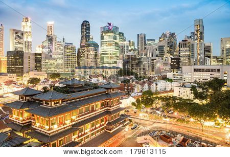 High view of Singapore skyline with skyscrapers and Tooth Relic Temple at blue hour - World famous top south east Asia destinations - City panorama on vivid warm filter with nightscape color tones