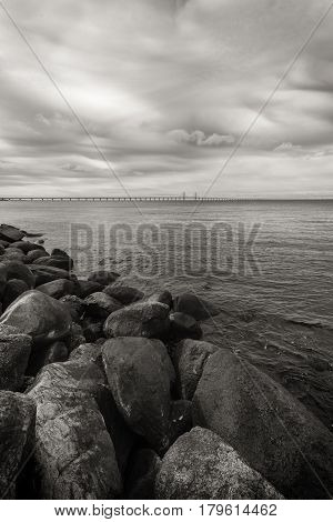 Large rocks on the sea shore seascape and Oresund bridge in the background on cold winter day with dramatic sky monochromatic
