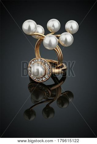 Two jewelry rings with pearls on black background