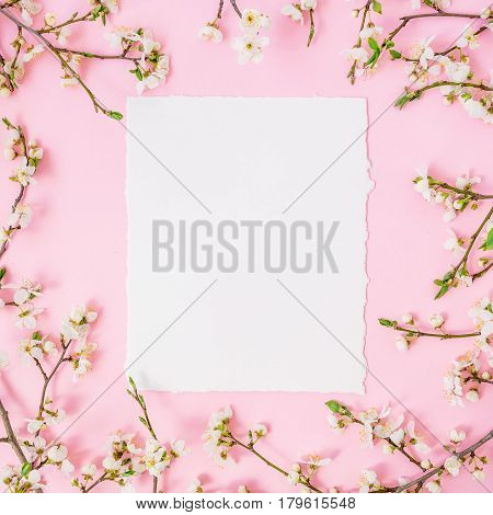 Frame of spring flowers and paper card on pink background. Flat lay, top view. Spring time background.