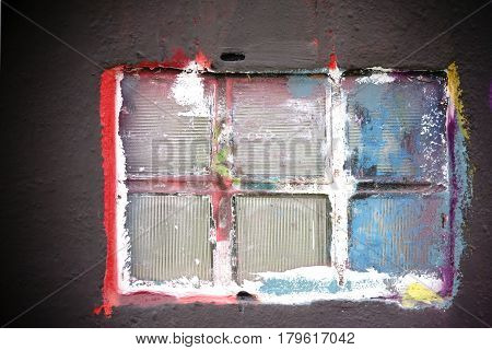 The closeup of a colorful painted window with glass tiles.