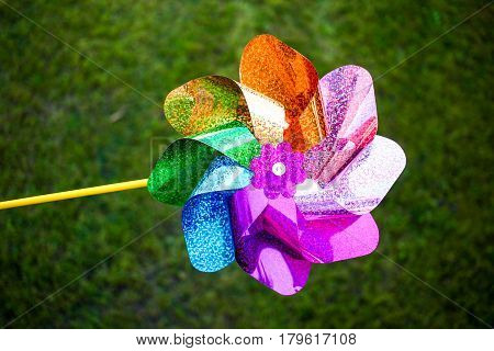 Multi Colored Pinwheel On Bright Vibrant Green Grass Background. Colors Of The Rainbow