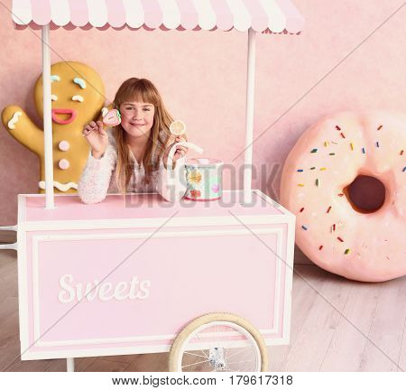 blond little girl with candy in confectionery styled pink room