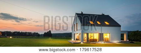 Photo of modern house with outdoor lighting at night external view
