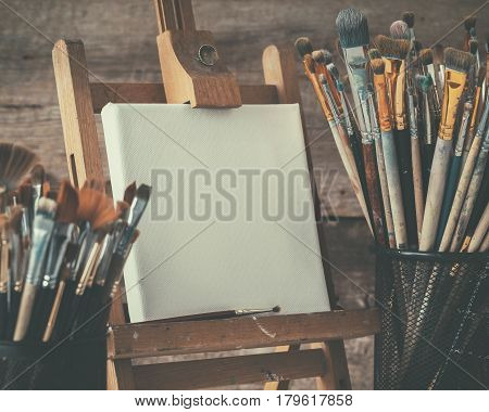 Artistic Equipment: Empty Artist Canvas On Easel And Paint Brushes In A Artist Studio. Retro Toned P